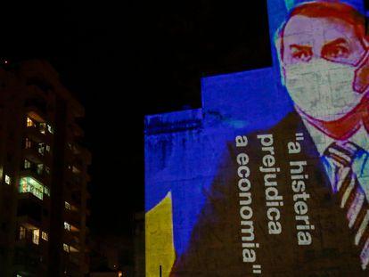 """Imagen de Bolsonaro con la frase """"La histeria daña la economía"""" proyectada contra un edificio."""