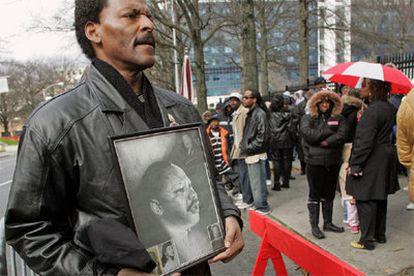 Un hombre muestra una foto de Martin Luther King ante la cola del funeral de Coretta King en Atlanta.