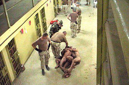 Un grupo de militares norteamericanos obligan a prisioneros iraquíes a amontonarse unos encima de otros.