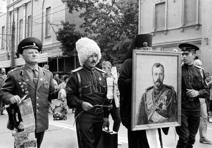 Pie de Foto: Dos soldados (uno de alta graduación), un cosaco y un pope portando un retrato del último zar, en Moscú tras el golpe de estado frustrado de 1991.
