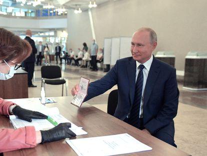 Putin enseña su pasaporte antes de votar, este miércoles en un colegio electoral de Moscú.
