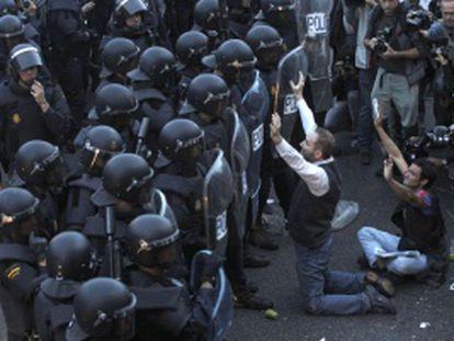 Dos manifestantes con los brazos levantados frente a dos filas de agentes antidisturbios en el 25-S.
