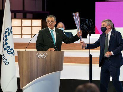 El director general de la OMS, a la izquierda, recibe del presidente del COI la antorcha olímpica.