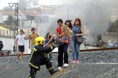 Un vecino traslada a una de las niñas heridas en el accidente de Santiago, momentos después del descarrilamiento.
