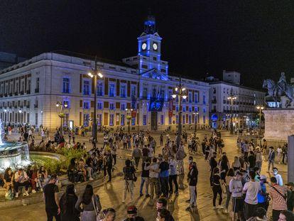 Decenas de personas en la Puerta del Sol de Madrid, pasadas las doce de la noche del sábado.
