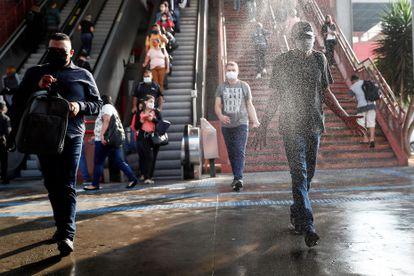 Los usuarios del metro pasan por una zona de desinfección al salir de una estación en la ciudad de Osasco, en el Estado de São Paulo.