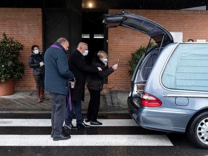 El cura José Luis Sáenz oficia la última oración a una víctima del coronavirus, un exboxeador. Su mujer rocía agua bendita sobre su ataúd, este lunes, en el cementerio Sur de Madrid.