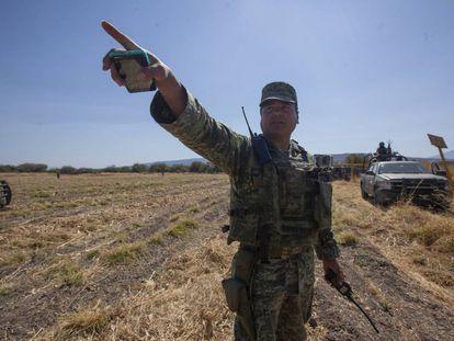 El teniente Armenta, en el campo que custodia en Guanajuato. Atrás, de amarillo, los indicadores del ducto de Pemex.