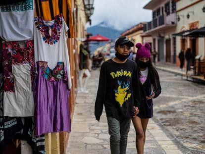 Dos jóvenes pasan frente a un puesto de artesanías en San Cristóbal de las Casas, Chiapas.