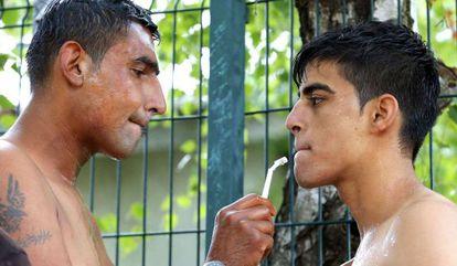 Inmigrantes afganos se afeitan en Subotica, junto a la verja.