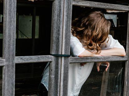 Una mujer reflexiona mientras mira por la ventana.