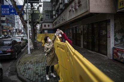 Una mujer recibe comida en la ciudad de Wuhan.