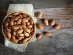 Almonds in wooden bowl on wood table,Top view.