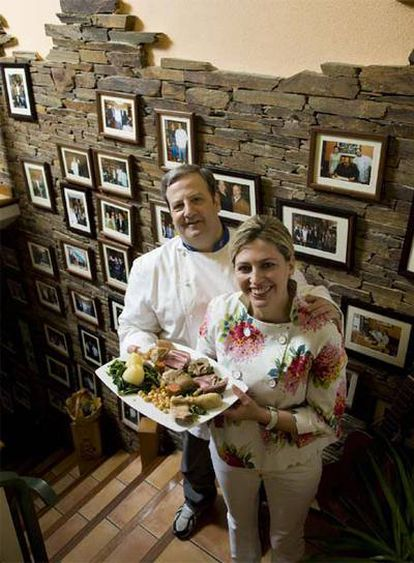 José Luis Iglesias y Áurea Vázquez, delante de la pared con fotografías de su restaurante.