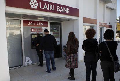 Clientes del Laiki Bank de Larnaca (Chipre) hacen cola en el cajero automático, ayer sábado por la mañana