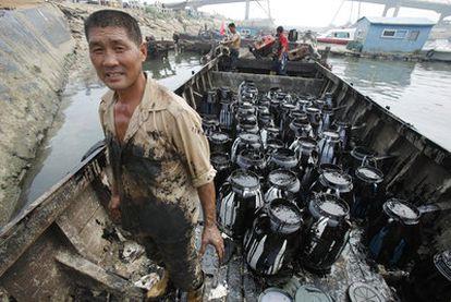 Un empleado recoge bidones llenos de petróleo del vertido en el puerto de Dalian.