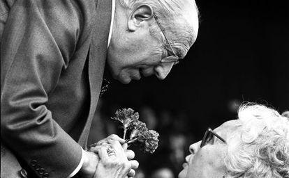 Enrique Tierno Galván, recibe un ramo de claveles de manos de una mujer, durante un acto en 1981
