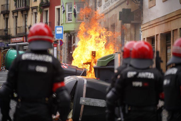 Agentes de la Ertzaintza observan como se quema un contenedor durante los altercados producidos en una manifestación contra el encarcelamiento de Pablo Hasél en Bilbao.