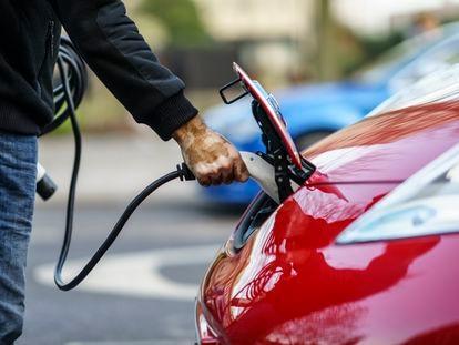 Un conductor carga su coche eléctrico en la calle.