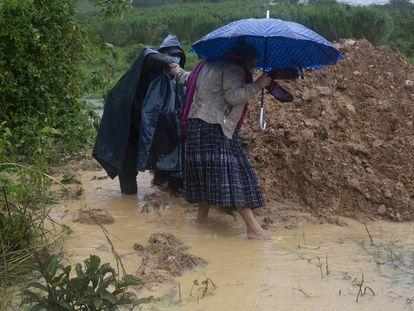Dos personas caminan en medio de las lluvias causadas por la tormenta tropical Eta, en Guatemala.