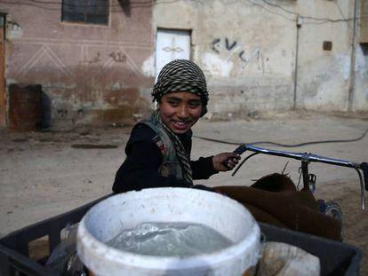 Un niño transporta el agua en una barrio de Damasco, este febrero.