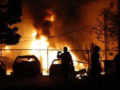 Un hombre mira el fuego de un vehículo en Minneapolis, este viernes.
