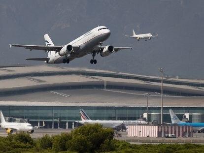 Un avión despega mientras otro aterriza simultáneamente en el aeropuerto de El Prat.