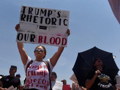 """Una mujer en El Paso el jueves pasado con un cartel que dice: """"La retórica de Trump es igual a nuestra sangre""""."""