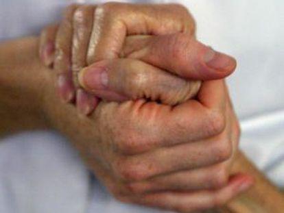 Una mujer mayor da la mano a su cuidadora.