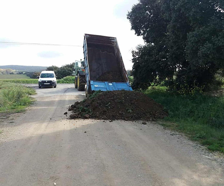Un camión vuelca arena para cerrar uno de los accesos de Setenil de las Bodegas.