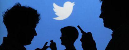 Gente con móviles en sus manos delante del logo de Twitter.