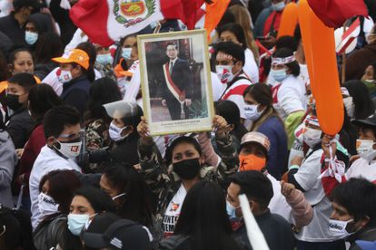 A Keiko Fujimori follower holds a portrait of Alberto Fujimori, her father, who ruled in an authoritarian manner in Peru from 1992 to 2000, at a June 3 rally in Lima.