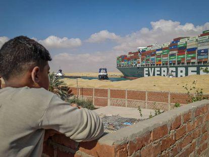 Un niño observa los trabajos de rescate en el canal de Suez.