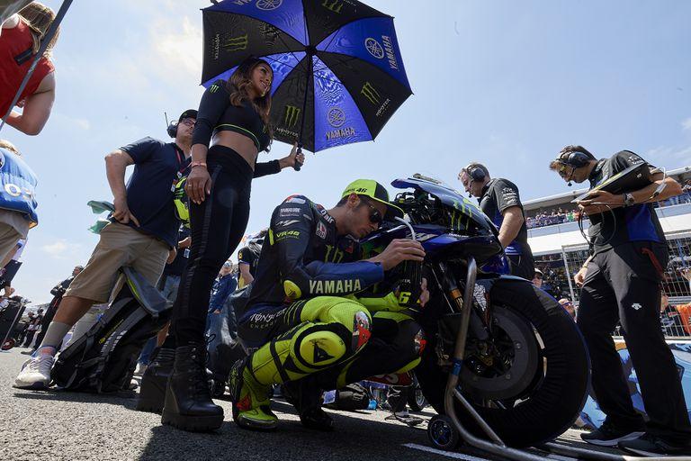 Una azafata protege del sol a Rossi antes de la carrera del GP de España, en Jerez, el año pasado.