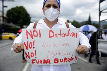 Una mujer muestra un cartel de protesta contra el Gobierno de Nayib Bukele, durante la manifestación de este miércoles, en San Salvador.