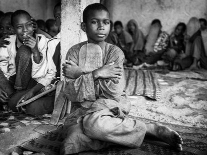 Los niños que acuden a las 'daaras' (escuelas coránicas no tendrían que mendigar para sobrevivir, pero en la práctica hay much)os niños por las calles de Senegal que piden unas monedas con la mano en alto mientras recitan el Corán. En 2010, Human Rigths Watch publicó un informe en el que apuntaba que al menos 50.000 niños viven internados en escuelas coránicas en Senegal sometidos a condiciones de vida parecidas a las de la esclavitud. En la imagen, un niño talibés abraza una de las tablas con el texto sagrado musulmán.