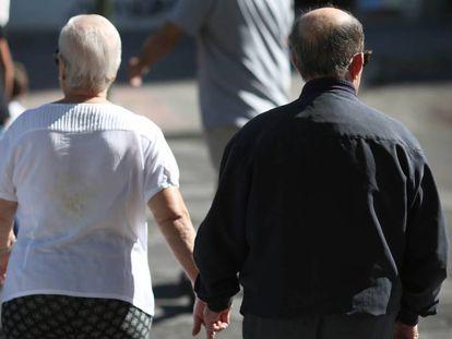 Una pareja de ancianos caminan de la mano en una calle de Madrid.
