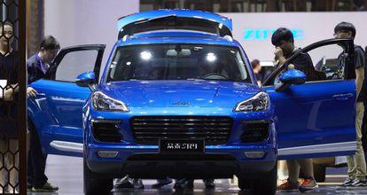 Visitantes de la feria del automóvil de Shanghái observan el coche Zotye SR9, muy parecido a  un Porsche Macan.
