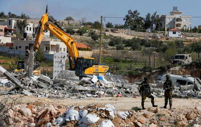Soldados israelíes vigilan la demolición de un edificio palestino, el lunes en Bani Naim (Cisjordania).