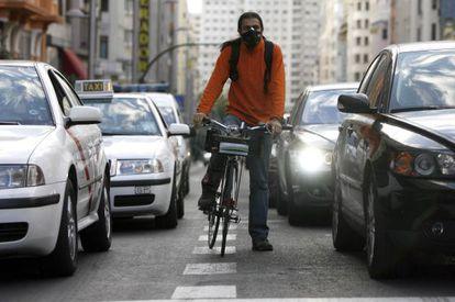 Un ciclista, con máscara para protegerse de la contaminación que producen los coches, circula por Madrid. / Samuel Sánchez