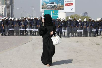 Una manifestante vistiendo un abaya camina frente a miembros de la policía antidisturbios en Manama, la capital de Bahréin, durante las protestas registradas el 13 de enero.