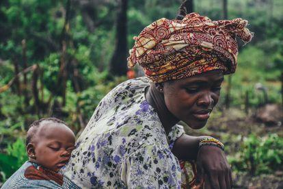 Una mujer con su bebé a cuestas en una plantación de yuca en Sierra Leona.