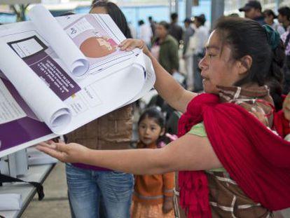 Una vocal de mesa coloca información electoral en un colegio en San Lorenzo Tlacoyucan, en la capital mexicana.