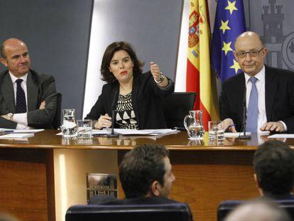 El ministro de Economía, Luis de Guindos (izquierda), junto a Soraya Sáenz de Santamaría y Luis Montoro.