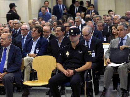 """Los acusados en el juicio contra los contra los expresidentes de Caja Madrid Miguel Blesa (d) y Rodrigo Rato (2-d) y otros 63 usuarios de las polémicas tarjetas """"opacas"""" de Caja Madrid."""