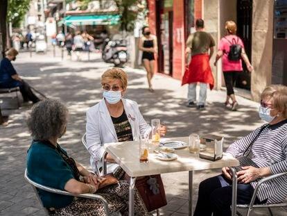 Isabel Cortes, junto a dos amigas, en la terraza de un bar de la calle Antonio López, en el barrio de Usera, Madrid, la semana pasada.