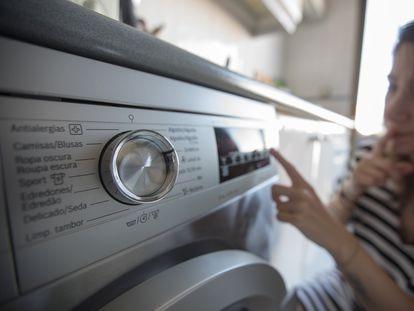 Una mujer pone la lavadora en su domicilio de Madrid.