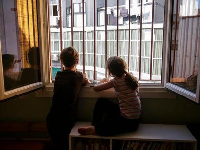 Dos hermanos miran por la ventana de su dormitorio durante el confinamiento en Madrid.