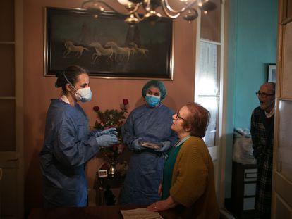 Las enfermeras Esther Caner y Cristina Menéndez conversan con Enrica Martinez (78 años) y Manolo Ortiz (79 años) en el comedor de su vivienda durante una visita.