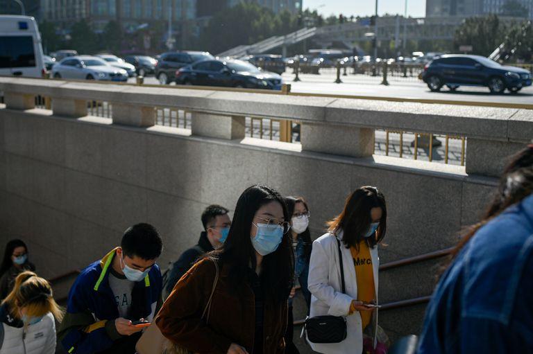 Un grupo de personas sale de un paso subterráneo en Pekín.
